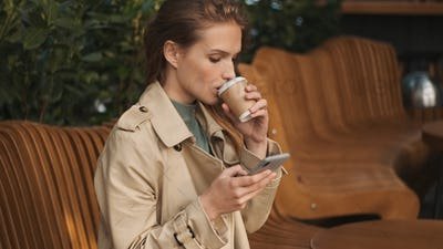 Beautiful girl dressed in trench coat watching social network du
