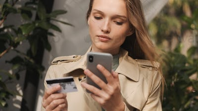 Gorgeous girl looking concentrated paying by credit card using s