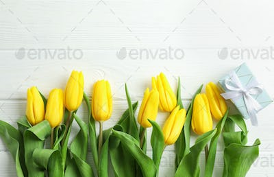 Beautiful yellow tulip flowers and gift box on wooden background. Space for text