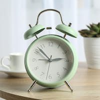 Beautiful retro alarm clock with cup of coffee and succulent plant on table against light background