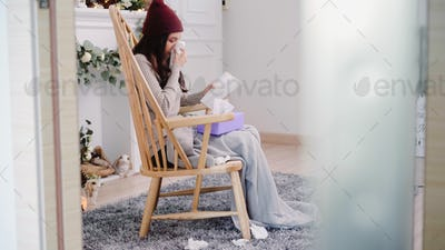 Asian woman feel headache wrapped blow the nose and use tissue relax in living room at home.