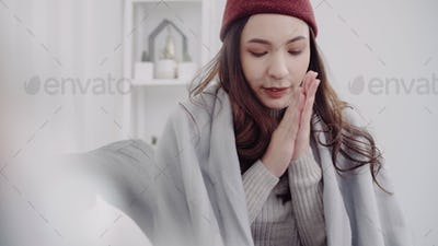 Asian woman feel headache wrapped in grey blanket blow the nose and use tissue.