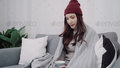 Asian woman feel headache blow the nose and use tissue relax in living room at home.