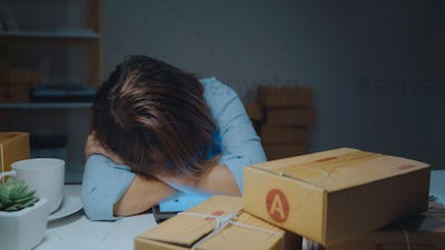 Asian entrepreneur business woman owner of SME sleepy exhausted working.