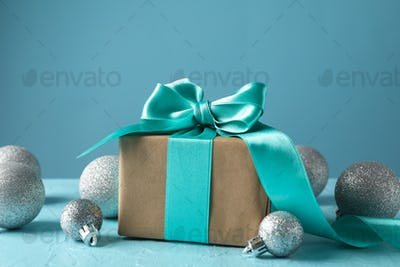 Gift box and glittering Christmas baubles on turquoise background, space for text