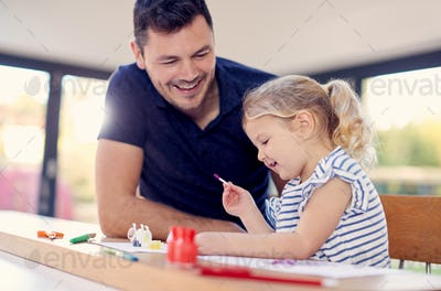 Father And Young Daughter Having Fun Doing Craft On Table At Home Together