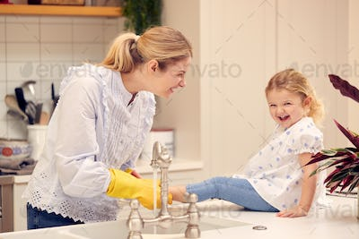 Mother And Daughter Having Fun In Kitchen Doing Washing Up At Sink Together