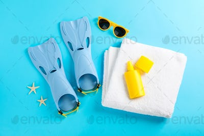 Flippers, sunglasses, towel and starfishes on color background, space for text