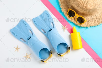 Flippers, sunglasses, straw hat, starfishes and sunscreen on color background