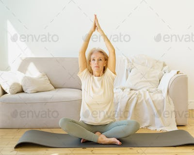 Retired woman in lotus pose practicing yoga exercises at home, sitting on mat