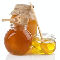 pot of honey and stick isolated on white