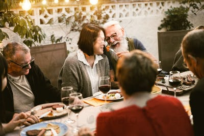 Happy senior people having fun at barbecue dinner - Main focus on senior man faces