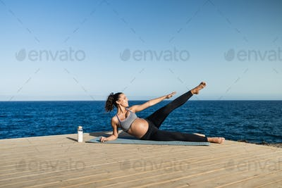 Young pregnant woman doing yoga outdoor - Sport exercises and maternity concept