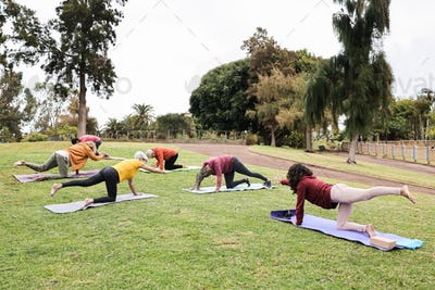 People doing yoga class while keeping social distance at city park - Main focus on center bodies