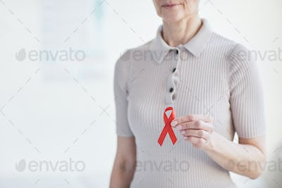 Woman holding red ribbon