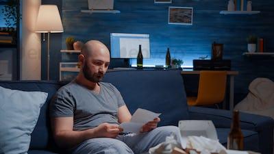 Desperate, depressed, helpless frustrated man reading banking bills