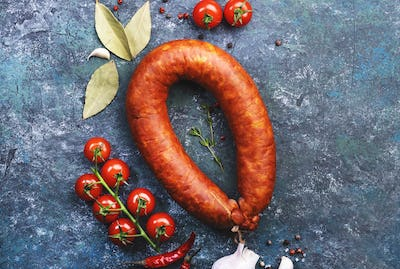 Smoked sausage circle on blue kitchen table with spices, tomatoes and garlic
