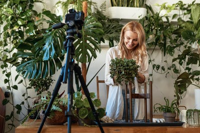 Cheerful blond haired woman recording a video in garden
