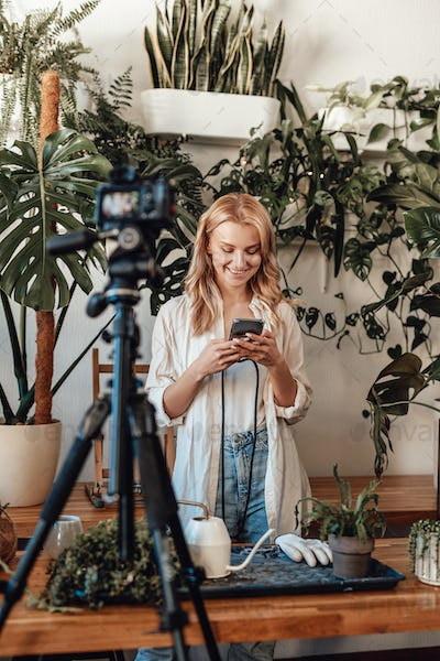 Female blogger with chatting on smartphone in garden with camera