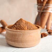 Bowl with cinnamon powder, cinnamon sticks and anise on white background, copy space