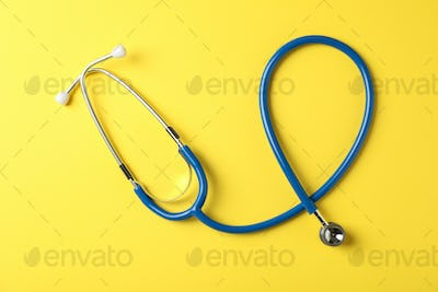 Stethoscope on yellow background, top view and space for text