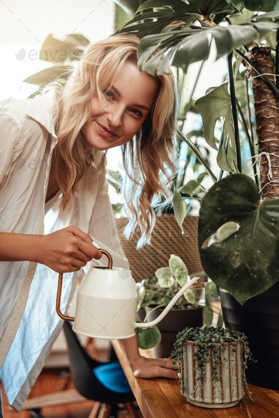 Joyful woman in casual clothing with watering can and houseplants
