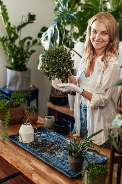 Satisfied young woman caring about houseplants at home