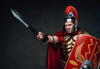 Angry roman soldier points sword against dark background