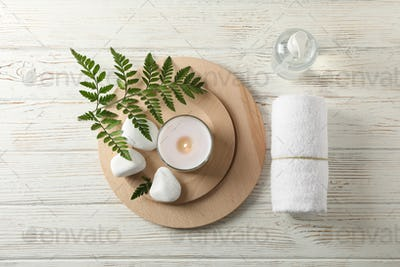 Spa accessories and fern branch on white wooden background, space for text