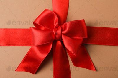 Red bow on craft background, close up