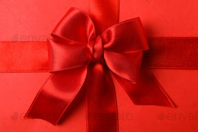 Red bow on red background, close up