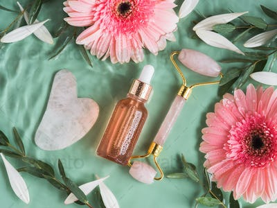 Cosmetic serum oil acid bottle with face pink quartz roller