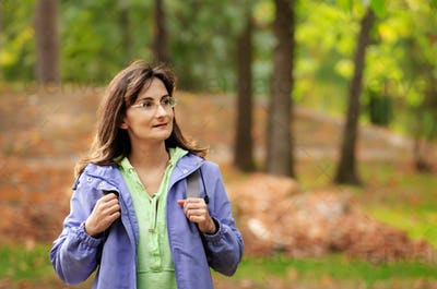 Middle aged active caucasian female model with backpack walk in woods autumn time