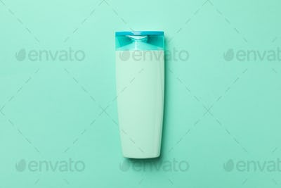 Blank bottle of shampoo on mint background, space for text