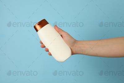 Female hand holds shampoo bottle on blue background, space for text