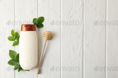 Natural hair care. Blank shampoo bottle and natural ingredients on wooden background