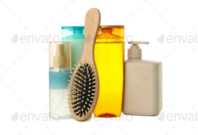 Blank cosmetics bottles and hair brush isolated on white background