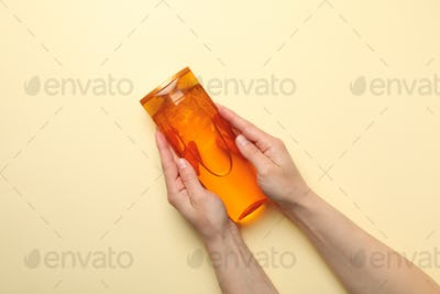 Female hands hold shampoo bottle on beige background, space for text