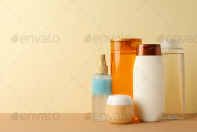 Blank cosmetic bottles on beige background, space for text