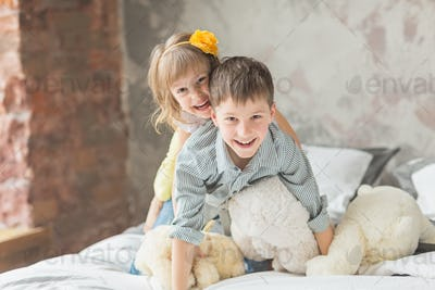 Brother and sister playing with teddy bear in bed