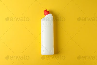 White bottle with detergent on yellow background, space for text