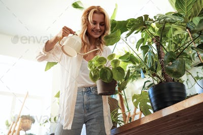 Portrait of a young woman caring about her houseplants at home