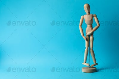 Wooden man hold his crotch on blue background. Urology