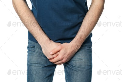 Man holding his groin, isolated on white background. Men's health
