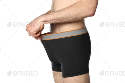 A man looks into his underpants, isolated on white background