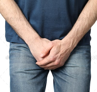 Man holds his crotch, isolated on white background