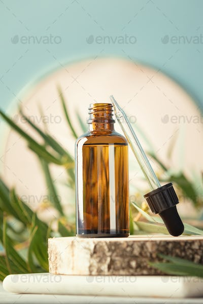 Blank transparent amber glass essential oil bottle and pipette on wooden slice podium