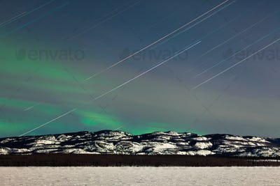 Star trails and Northern lights in moon lit night