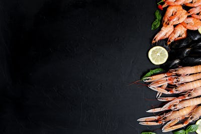 Healthy fish and seafood assortment on black background. Seafood on black rustic background.