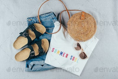 Flat lay with summer women's clothing and accessories. White t-shirt, denim shorts, rattan bag.
